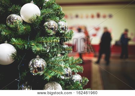 Christmas tree in lobby of shop on background of people walking, photo toned