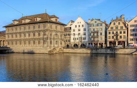 Zurich, Switzerland - 19 December, 2016: the Limmat river and old town buildings along it. The leftmost building is the Zurich Town Hall (German: Rathaus), housing the city and canton parliaments.