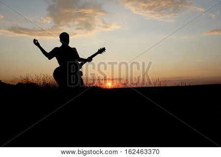 silhouette of the guy with a guitar on a sunset background