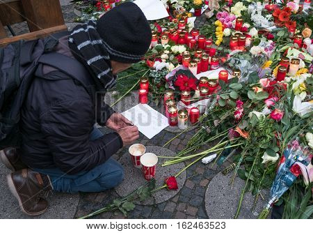 Berlin Germany - december 20, 2016: Man put candle and flowers at the Christmas Market in Berlin the day after a truck drove into a crowd of people.