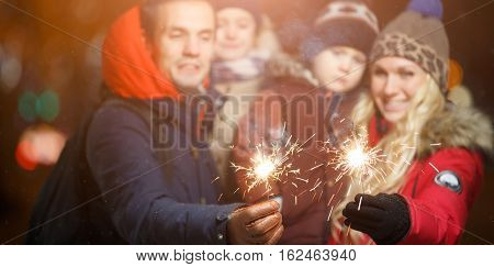 Family with children with Bengal lights in park at night in new year