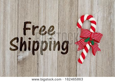 Christmas free shipping message A red and white candy cane on weathered wood background with text Free Shipping