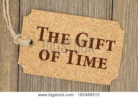 Old fashion time gift tag A retro cork gift tag on weathered wood background with text The Gift of Time