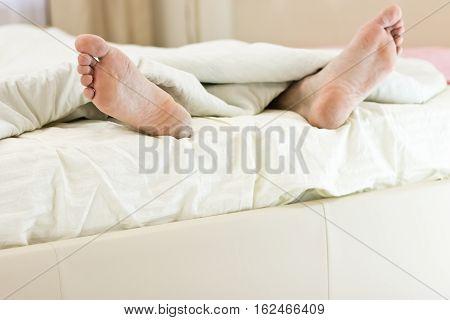 Men Feet Alone In A Bed.