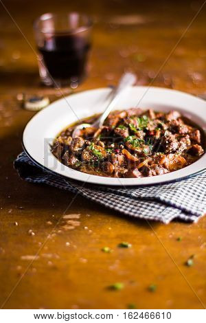 Portion of traditional irish beef and guinness beer stew with carrots and fresh parsley in a plate ready to serve, selective focus