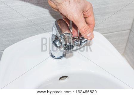 Human hand opens bidet mixer for water