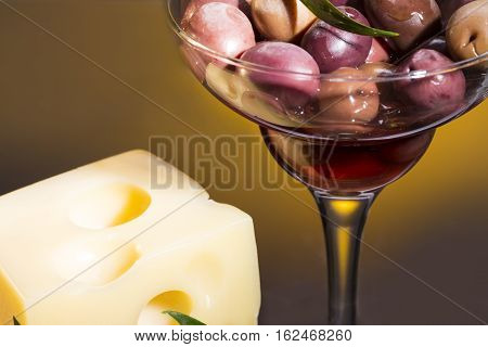 Large olives and olive branch in the glass on a yellow background