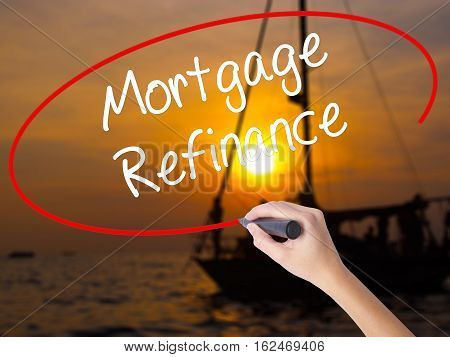 Woman Hand Writing Mortgage Refinance With A Marker Over Transparent Board