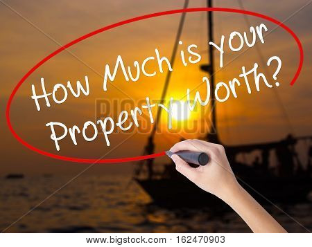 Woman Hand Writing How Much Is Your Property Worth? With A Marker Over Transparent Board