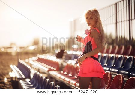 Young woman runner resting after workout session on sunny morning. Female fitness model sitting on volley ball seats on the beach. Female jogger taking a break from running workout.