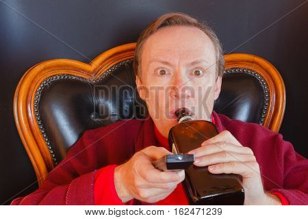 a man lying on the couch with a wine bottle is devouring the last episode of a tv show / a sick man of tv series