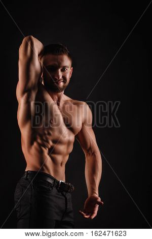 Bodybuilder posing on a black background. Dramatic portrait of an athlete.  Relief and sculptural muscles of the body. Healthy lifestyle concept. Abdominal muscles and shoulders triceps.