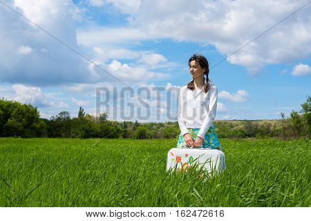 Smiling girl in anticipation of the travel standing in a field holding a white suitcase with a pattern.