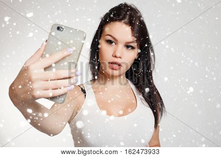 winter christmas people beauty concept-Portrait of a Beautiful successful smiling girl doing selfie in a white shirt on a light background over snow background