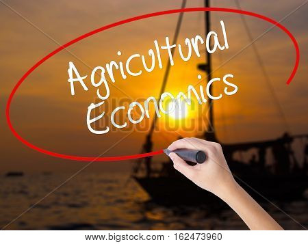 Woman Hand Writing Agricultural Economics With A Marker Over Transparent Board