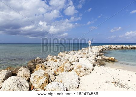 The line of stone to make a natural sea pool on Grand Cayman island Seven Mile beach (Cayman Islands).