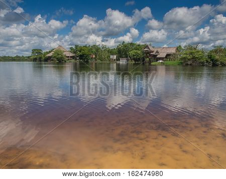 Sky trees and houses reflected in the river in the late afternoon Santo Tomas Peru