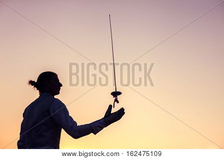 Silhouette Of Fencer Man Throwing Up His Fencing Sword