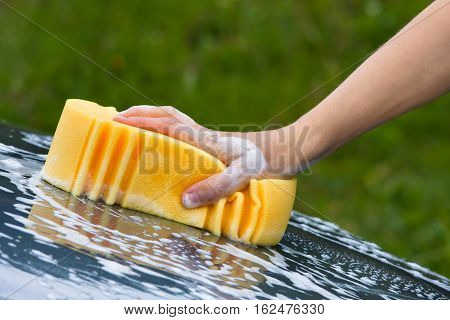 hand washing the windscreen of car with sponge
