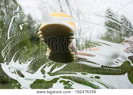 hand washing window of car with sponge inside view