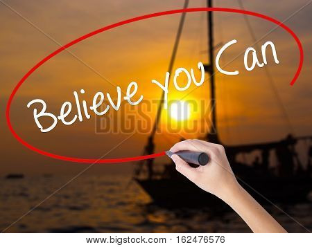 Woman Hand Writing Believe You Can With A Marker Over Transparent Board