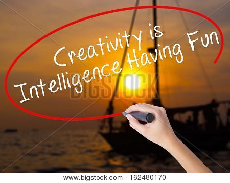 Woman Hand Writing Creativity Is Intelligence Having Fun With A Marker Over Transparent Board