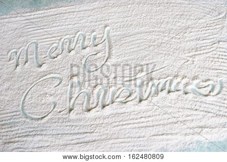 A festive Christmas greeting is wrote in the flour during the holiday baking in the kitchen.
