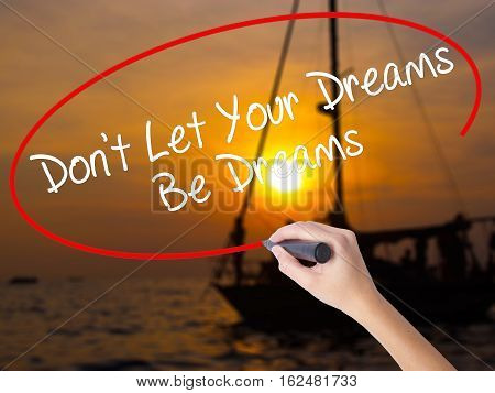 Woman Hand Writing Don't Let Your Dreams Be Dreams With A Marker Over Transparent Board