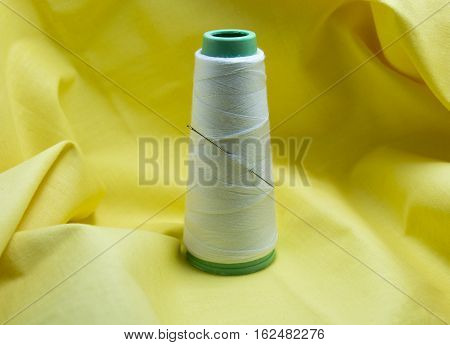 Spool of white tread and a needle on yellow textile background