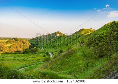 Path at the foot of ridge chalk hills. Green hills under blue sky.