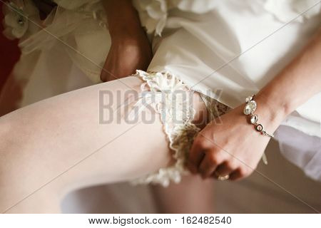 Bride adjusts a lace garter on a stocking