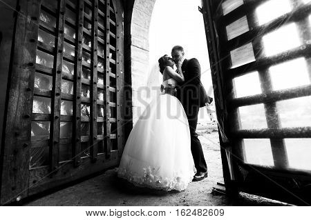 Bride Kisses Fiance's Cheek Standing In The Open Gates