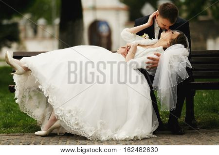 Bride lies on fiance's knees and kisses him
