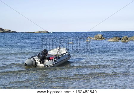 Gray motor rubber inflatable boat with fishing tackles in bay