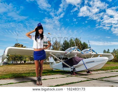 Attractive young stewardess smiles near small airplane