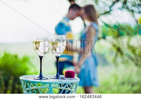 Love, Family, Anniversary Concept - Wine Glasses And Ring Box In Focus With Engaged Couple On The Ba