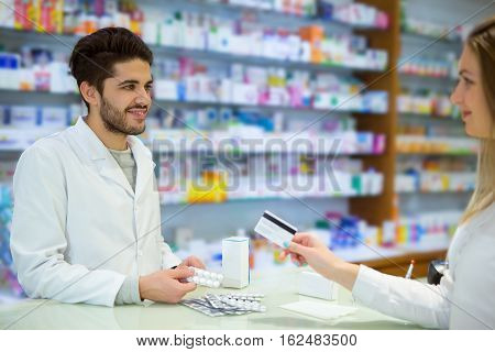 Experienced pharmacist counseling female customer in modern pharmacy and woman pays with credit card