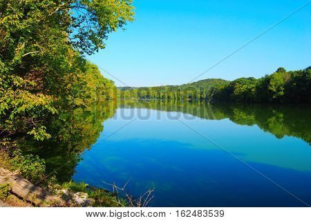 Sunny lake landscape surrounded by luscious woods.