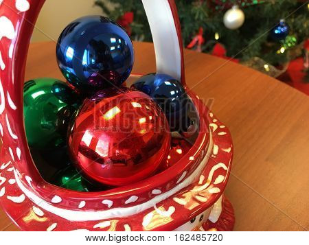 Christmas Colorful Bright Shining Decorations in decorative basket next to Christmas tree on wood table at the office for holiday office tree decorating room for copy space