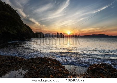Seascape of Kamchatka Peninsula: beautiful view of sunset over Three Brothers Rocks in Avacha Bay (Pacific Ocean). Kamchatka Region Russia Far East Eurasia.