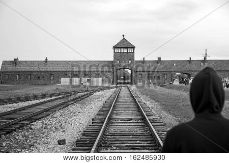 Person standing at Rail entrance to concentration camp at Auschwitz Birkenau KZ Poland 2