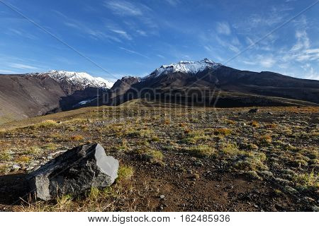 Panoramic volcanic landscape of Kamchatka Region: autumn view of Kozelsky Volcano on background of blue sky. Avachinsky-Koryaksky Group of Volcanoes Kamchatka Peninsula Russian Far East Eurasia.