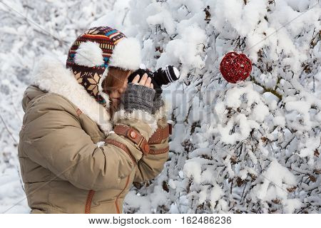 Beautiful young woman in down-padded coat fingerless mittens and ornamented hat photographing red original designed rattan christmas ball in snowy winter forest by a knitted camera.