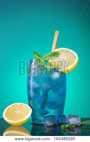 Blue cocktail with a slice of lemon ice and mint. A glass with a blue lagoon alcohol cocktail on a blue background.
