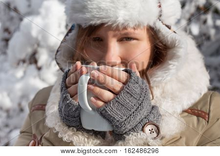 Woman In Grey Mittens, Coat And Hat With White Fur Drinking From Cup At The Background Of Winter For