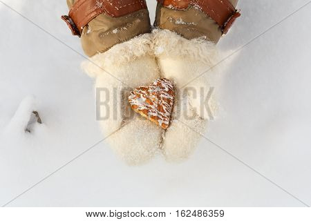 Female Hands In Woollen White Mittens Hold Beautiful Heart Shaped Biscuit Cookie With Icing At Snow