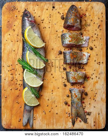 Whole And Cut Grey Mullet Fishes Lie On Light Wooden Cutting Board With Lemon Segments, Rosemary Bra