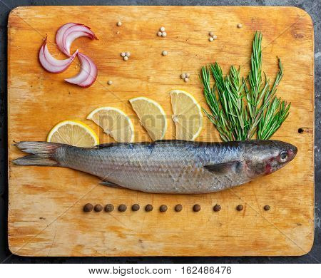 Raw Fresh Grey Mullet Fish Lies On Light Wooden Cutting Board With Composition Of Lemon Segments, On