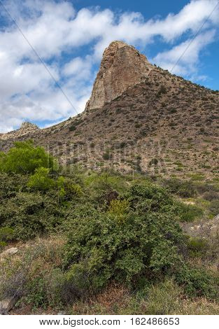 A sheer rock faced mountain rises out of the rugged arid land of southern New Mexico beneath a beautiful early summer sky.