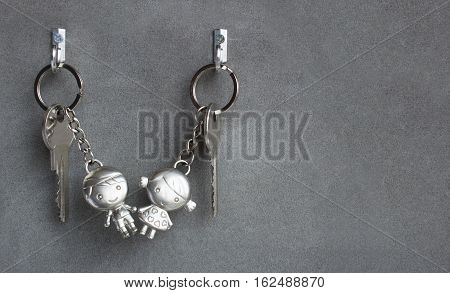 Keyrings boy and girl pulling hands. Lovers keychains love. Gray background